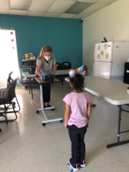 Marcia demonstrates our new method of screening by using a 2.5 foot long vertically  adjustable table which allows for at least a six foot distance between the screener and the child